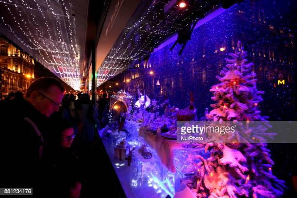 People stare at a shop window during Christmas in Paris France on November 25 2017