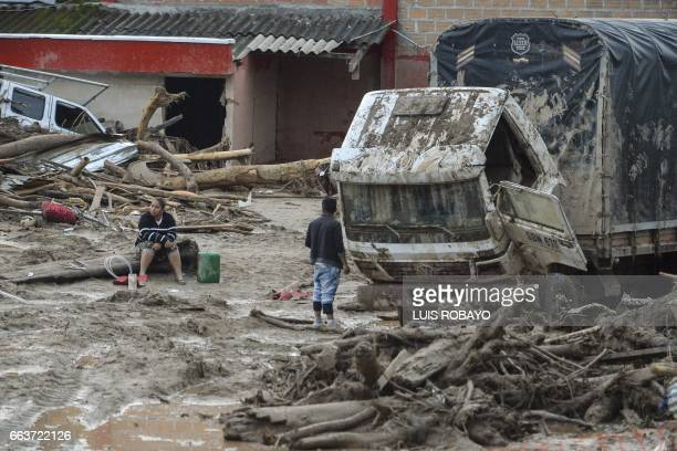 TOPSHOT People stare at damages caused by mudslides following heavy rains in Mocoa Putumayo department southern Colombia on April 2 2017 The death...