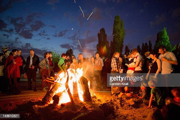 People stay around a campfire during the celebrations of Walpurgis Night at the Mauerpark on April 30 2012 in Berlin Germany Hundreds of people...