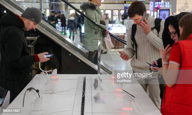 People stay around the Apple promoting table at one of shopping malls in Kyiv Ukraine Dec12 2017 iPhone X official sales started in Ukraine