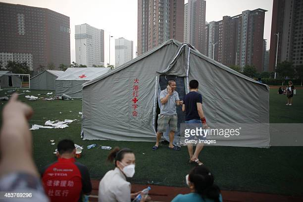 People stay at a primary school set as the emergency evacuation after the Wednesday explosions of a warehouse in Binhai New Area on August 13 2015 in...