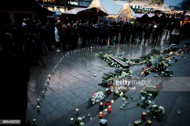 People stay at the memorial to victims following its inauguration at the site of the 2016 Christmas market terror attack at Breitscheidplatz on the...