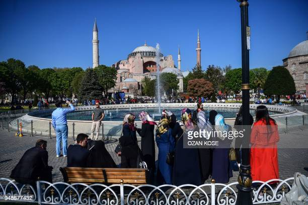 People stay in front of a fountain as Hagia Sophia is seen in backround on April 19 2018 in Istanbul