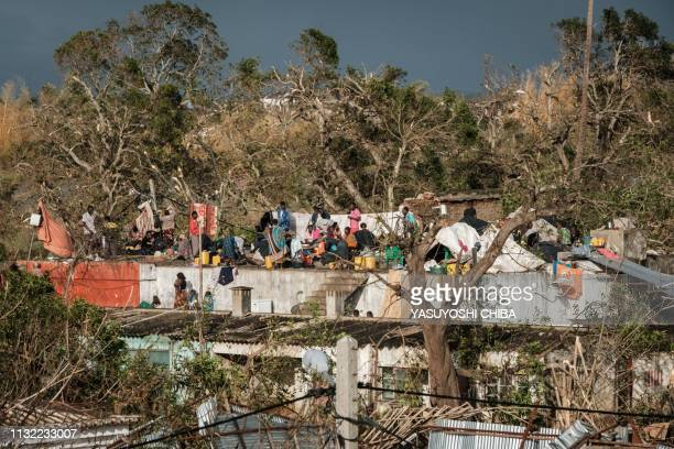 People stay in shelter on a rooftop of a commercial building in Buzi Mozambique on March 23 2019 The death toll in Mozambique on March 23 2019...