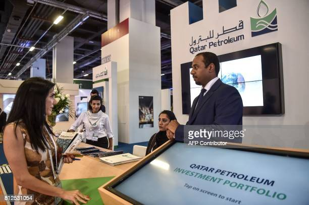 People stay next to the Qatar petrolium stand on July 11 2017 during 22nd World Petroleum Congress in Istanbul Oil major bosses and energy ministers...