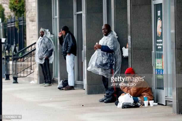People stay out of the rain on Adams St. In Detroit, Michigan on April 7, 2020. - The Detroit News is reporting a total of 734 employees at the Henry...