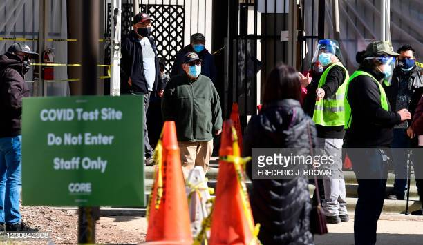 People stepping out of a Covid vaccine location are directed by a volunteer wearing a face mask and shield to a waiting area in Los Angeles,...