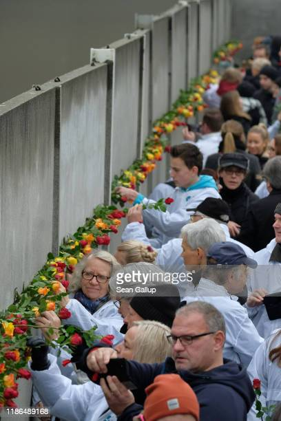 People stick flowers into slats of a stillstanding portion of the Berlin Wall at Bernauer Strasse following a ceremony to celebrate the 30th...