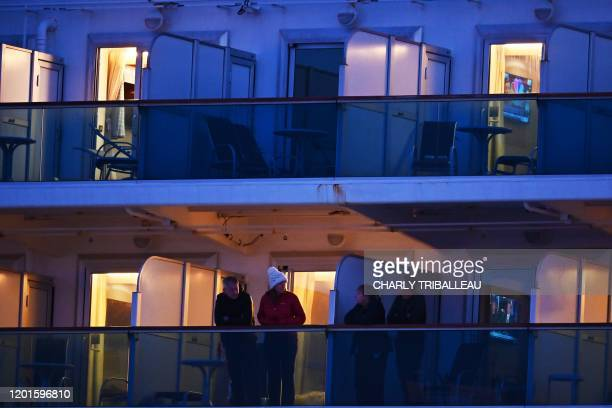 People still in quarantine due to fears of the new COVID19 coronavirus stand on balconies of the Diamond Princess cruise ship docked at the Daikoku...