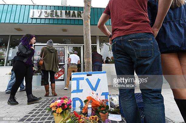 People stop at a makeshift memorial in front of IV Deli Mart, one of the locations of a drive-by shooting last night, in Isla Vista, California, a...