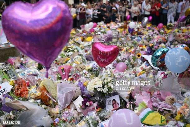 TOPSHOT People stop by a mass of flowers to observe a minute's silence in St Ann's Square in Manchester northwest England on May 25 as a mark of...