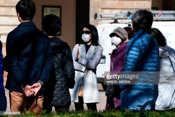 People stop outside the Teatro alla Scala in the northern city of Milan on February 28 2020 Italy urged tourists spooked by the novel coronavirus...