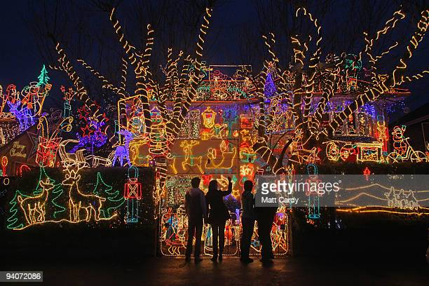 People stop to admire Christmas festive lights displayed on a detached house in a suburbian street on December 5 2009 in Melksham England The lights...