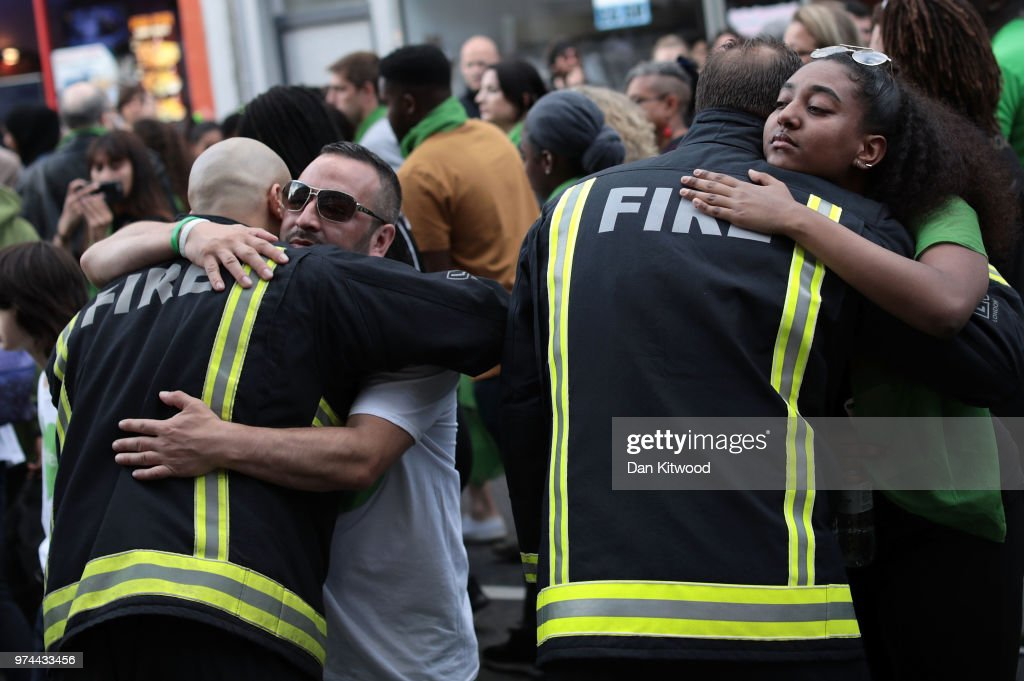 People stop to hug firefighters during a silent march to St Mark's Park (Kensington Memorial Park) where an open Iftar will take place on the one year anniversary of the Grenfell Tower fire on June 14, 2018 in London, England. In one of Britain's worst urban tragedies since World War II, a devastating fire broke out in the 24-storey Grenfell Tower on June 14, 2017 where 72 people died from the blaze in the public housing building of North Kensington area of London.