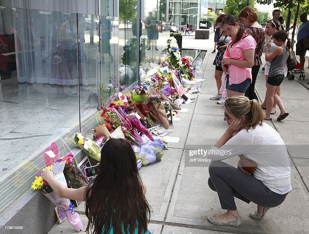 People stop to look at a memorial to deceased actor Cory Monteith outside the Fairmont Pacific Rim Hotel on July 16, 2013 in Vancouver, British Columbia, Canada. The B.C. Coroners Service released results of Monteith's autopsy today and found the 31-year-old's cause of death was a mixed drug toxicity involving heroin and alcohol.