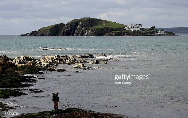 People stop to look at Burgh Island said to be a source of inspiration for Agatha Christie as they walk on the beach close to the picturesque seaside...