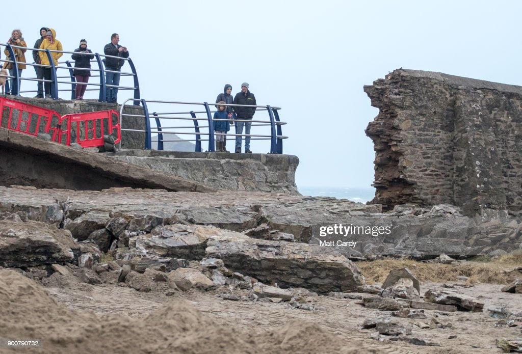 People stop to look at the damage to the harbour wall that was caused last night in Storm Eleanor in Portreath on January 3, 2018 in Cornwall, England. Overnight Storm Eleanor brought 70-100mph gusts and torrential rain to some parts of the UK and Ireland creating floods and cutting electricity supplies in some areas. A yellow warning by the Met Office is still in force.