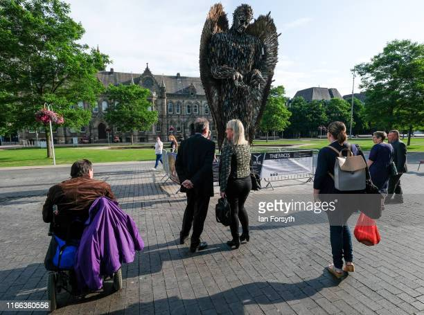 People stop to look at the Knife Angel sculpture installed in the Centre Square in Middlesbrough on August 06 2019 in Middlesbrough England The 27ft...