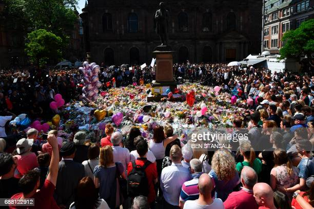 TOPSHOT People stop to observe a minute's silence in St Ann's Square gathered around the tributes in central Manchester northwest England on May 25...