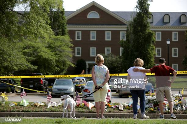People stop to pay their respects to those killed in a mass shooting at a makeshift memorial outside the City of Virginia Beach Operations Building...