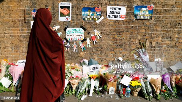 People stop to read tributes and look at plawers placed in the Finsbury Park area of north London on June 20 for the victims of a van attack on...