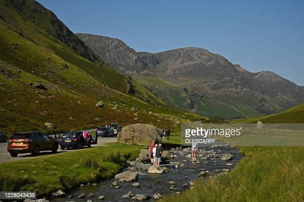 People stop to take photographs in a stream on Honister Pass in the Lake District in north west England on August 14 as many people take advantage of...