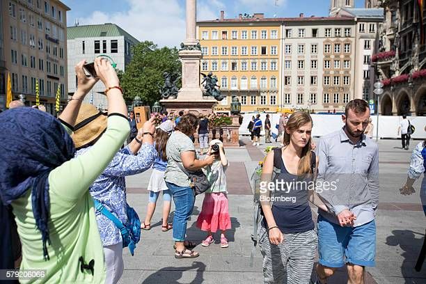 People stop to take photographs in front of the Town Hall in Marienplatz in Munich Germany on Saturday July 23 2016 German Chancellor Angela Merkel...