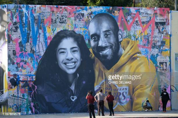 People stop to take pictures in front of the new mural by French artist Mr Brainwash picturing Kobe Bryant and his daughter Gigi in Los Angeles on...