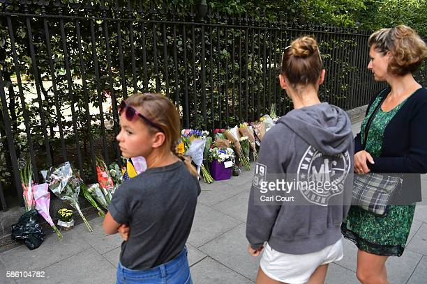 People stop to view flowers laid at the scene of a stabbing in which one woman was murdered on August 5 2016 in London England Darlene Horton a...