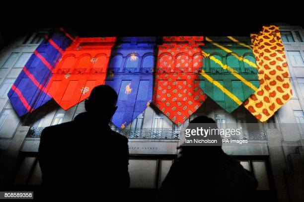People stop to watch a 4D display projected onto the front of the Ralph Lauren store in London's New Bond Street