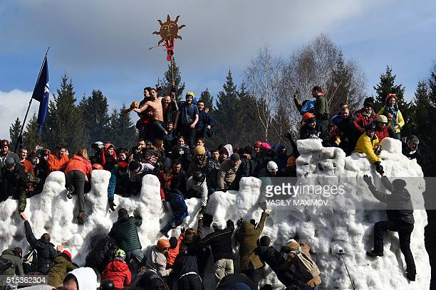 People storm a snow fortress close to the village of Abramtsevo 60 km north of Moscow on March 13 in celebration of Maslenitsa a farewell ceremony to...