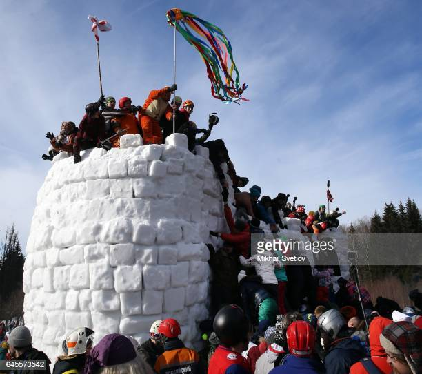 People storm the snow fort during the celebration of Maslenitsa also know as Shrovetide or Butter Week held to mark the end of winter in the forest...