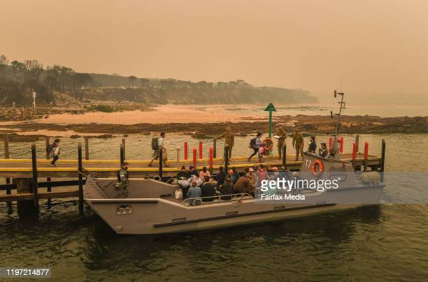 People stranded in Mallacoota Victoria are evacuated by army personnel to the HMAS Choules after bushfires ravaged the town on December 30th on...
