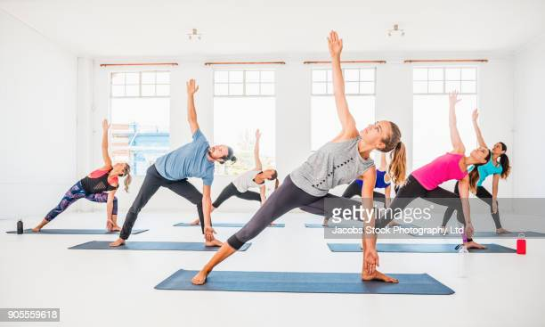 people stretching in yoga class - dansstudio stock pictures, royalty-free photos & images