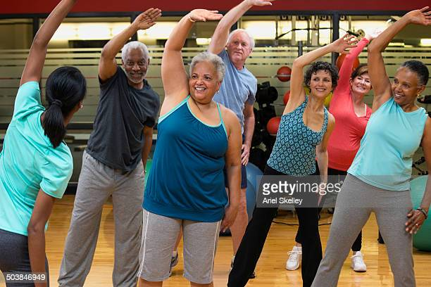 people stretching together in exercise class - fat black man stock photos and pictures