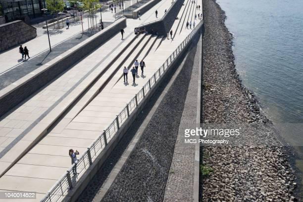 menschen flanieren entlang einer promenade in köln - uferpromenade stock-fotos und bilder