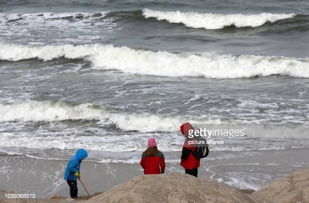 People stroll along the beach during strong winds at the seaside resort Kuehlungsborn Germany 07 March 2013 Meteorologists forecast weather to change...