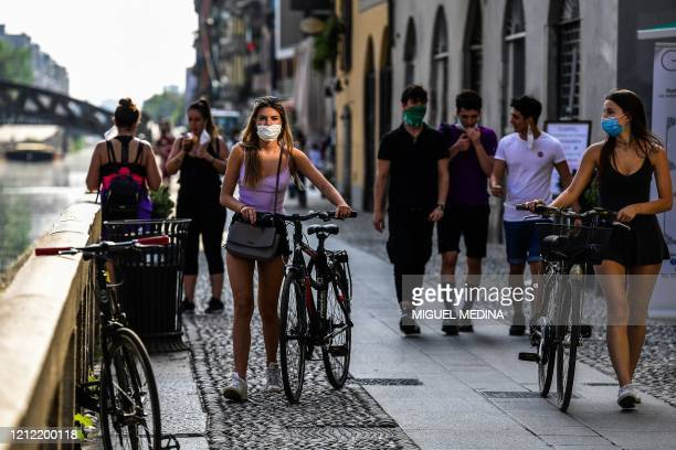 People stroll along the Navigli canals in Milan on May 8 2020 during the country's lockdown aimed at curbing the spread of the COVID19 infection...