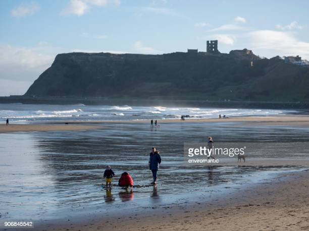 people stroll and play in the sands at north marine drive in scarborough in the cold winter with scarborough castle in the background. - scarborough uk stock photos and pictures