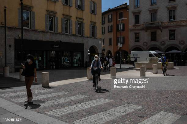 People stroll and ride bicycles along a pedestrian street in the Lower Town on June 18, 2020 in Bergamo, Italy. The city of Bergamo is slowly...