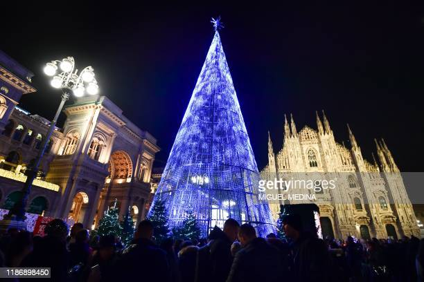 People stroll by a giant light Christmas tree on Piazza del Duomo in Milan on December 7, 2019.