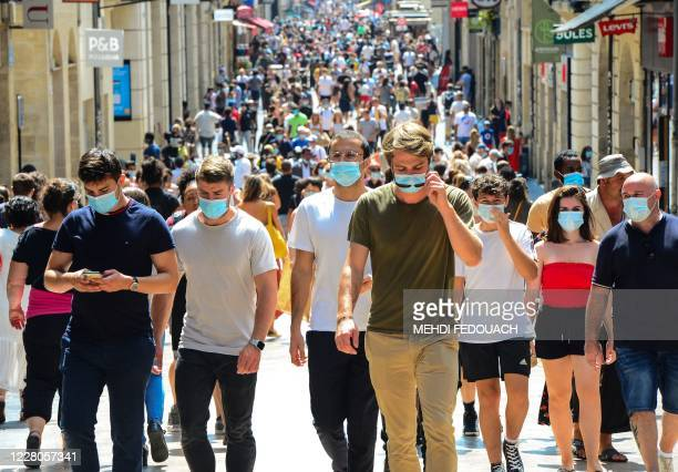 People stroll down Bordeaux's main shopping street Sainte-Catherine, where wearing a mask is compulsory as of August 15 to prevent the spread of the...