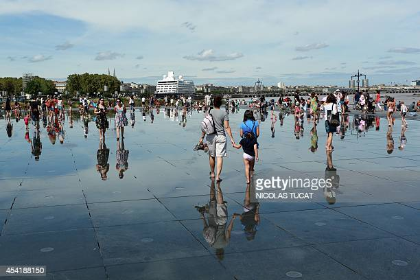 People stroll in the Water Mirror on August 25 2014 in the southwestern French city of Bordeaux Hardly eight years after its creation the Water...