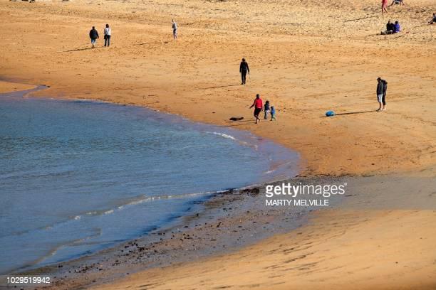 People stroll on Kaiteriteri beach in Golden Bay, in Nelson on September 8, 2018.