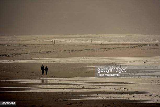 People stroll on the beach at St Ouen's Bay on March 1 2008 in Jersey Channel Islands Britain's most southerly island Jersey is located 100 miles...