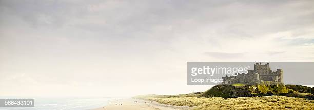 People strolling along the sandy beach by Bamburgh Castle on the Northumberland Coast