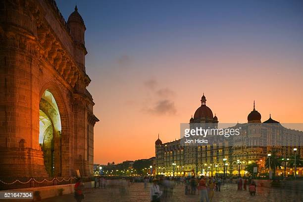 people strolling between the gateway of india and the taj mahal palace hotel - mumbai stock pictures, royalty-free photos & images