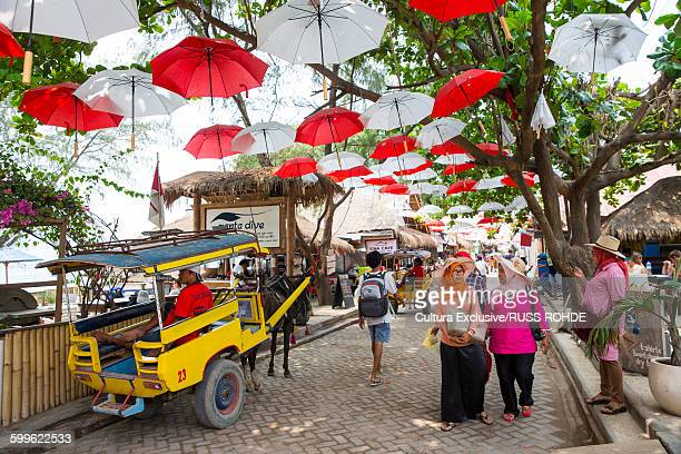 people strolling on promenade under red and white umbrellas, gili trawangan, lombok, indonesia - gili trawangan stock photos and pictures