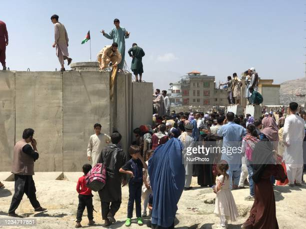People struggle to cross the boundary wall of Hamid Karzai International Airport to flee the country after rumors that foreign countries are...