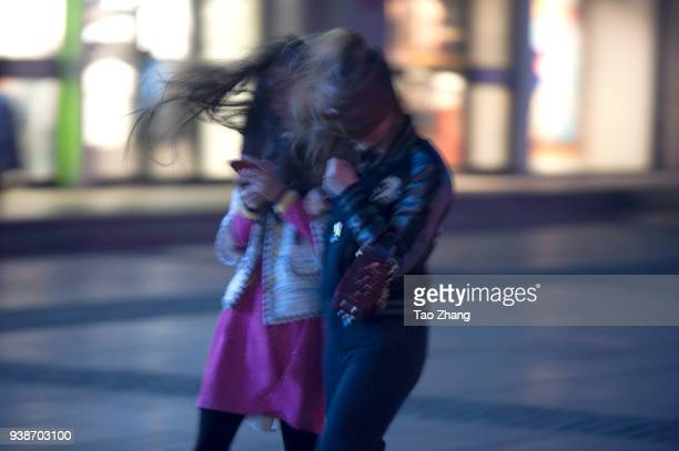People struggle with strong wind after a moderate gale warning was issued on March 27 2018 in Harbin China